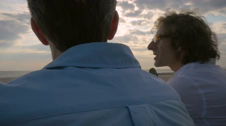 companionship : Hand held slow motion shot of two men talking while watching the sunset over the ocean at the beach.