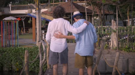 companionship : Slow mo of two middle aged male best friends or brothers putting their arms around each other while walking away from the camera on a wooden bridge.