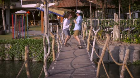 companionship : Two grown men brothers or friends playing together with pretend fighting and jumping on a wooden bridge as they walk closer towards the camera in slow motion.