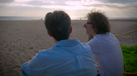 melhor : Two middle aged men sitting together and watching the sunset while talking with each other in slow motion. Vídeos