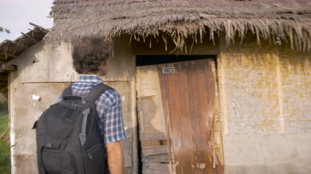 crummy : A tourist wearing a backpack approaches an abandoned home and knocks on the door. This hand held shot follows this confused man to his poor vacation rental. Stock Footage