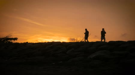 viciado : Silhouette of people walking by one after another on their cell phones ignoring the beautiful sunset behind them