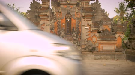 caos : A single chicken walks in front of a Hindu temple in Bali, Indonesia as cars, motorbikes, and traffic drive by. Nobody notices this calm place of worship amongst the chaos of the city. Vídeos