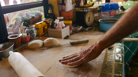 piekarz : Side profile of an active and attractive senior man working a dough ball with his hands in his kitchen as he prepares to make bread or pizza - hand held with a push-in to see the dough on a wooden cutting board while he sprinkles it with flour.