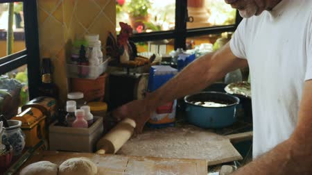 esneme : Tilt up and down of a man preparing bread or dough with a rolling pin for pizza on a wooden cutting board in his home kitchen Stok Video