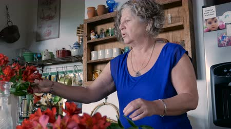 buket : An Israeli woman in her 60s arranges fresh cut red lily flowers in a vase in her modern kitchen in warm weather - dolly shot