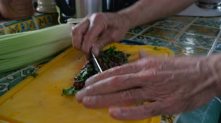 cozinhar : Close up of food and then pull out to reveal an elderly man chopping fresh parsley with raw liver of a cutting board with a knife by hand in his kitchen. Stock Footage