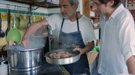 pascha : An elderly Jewish man removes cooked chicken livers and eggs from a pot with an younger man watching and learning how to prepare chopped liver for a passover seder dinner - hand held Wideo