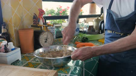 pascha : Baby boomer man vigorously mixing a bowl of matzo balls in a modern kitchen - medium shot