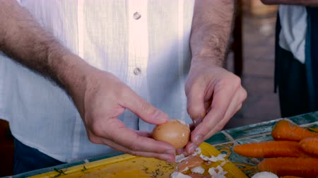 pascha : A middle aged man peels a hard boiled egg while working beside an elder man in a home kitchen - pan up