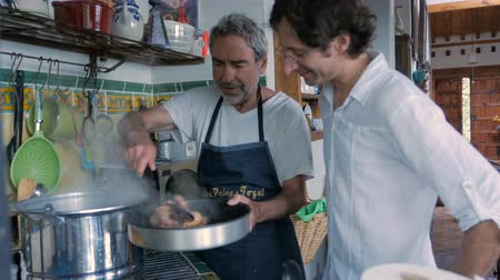 cozinhado : A father and son work together in a kitchen removing cooked liver and hard boiled eggs from a large pot in preparation for a Passover seder dinner. Vídeos