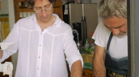 pascha : A mature father and middle aged son work together in the kitchen grinding fish for Passover seder meal Wideo