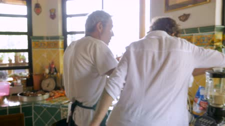 pascha : The camera follows a father and son working together in the kitchen cooking and using a meat grinder - hand held