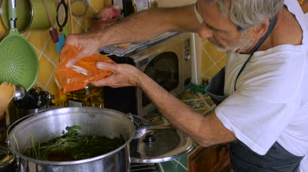 pascha : An elderly man adds paprika from a plastic bag to a pot of chicken soup in his kitchen without measuring the amount