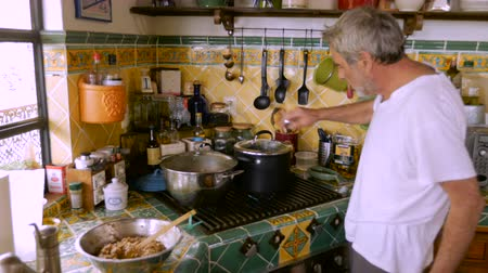pascha : An elderly man lighting a gas stove and checking a pot of steaming food