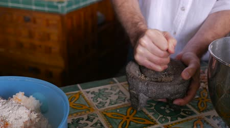 pascha : Slow motion of a man grinding pepper in a mortar and pestle