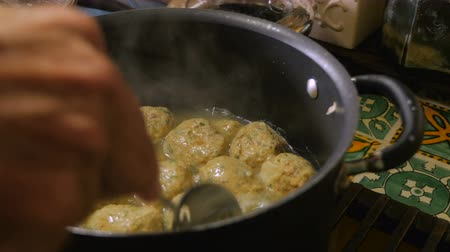 пельмени : Close up of a mans hand stirring and cooking matzah ball soup in a large pot with a spoon.