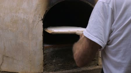żyd : A man places home made matzah from a wooden paddle into a wood fired oven in slow motion Wideo