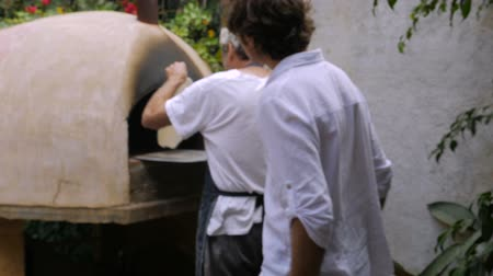 pascha : An older man flips homemade matzah in a wood burning oven while a middle aged man watches over his shoulder in slow motion and hand held