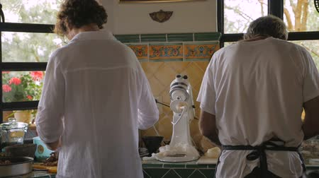 pascha : Two men preparing food in a kitchen shot from behind in slow motion