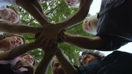 trabalho em equipe : Low angle shot from below of a multi generational group of people who place their hands together in the center of a circle and then cheer in a celebration of a successful event.