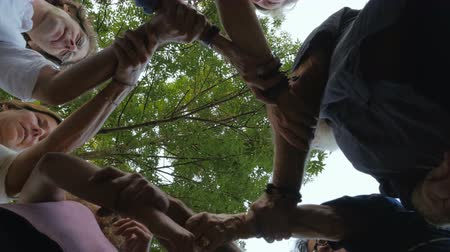 interlock : A group of people interlock their arms together in unity Stock Footage