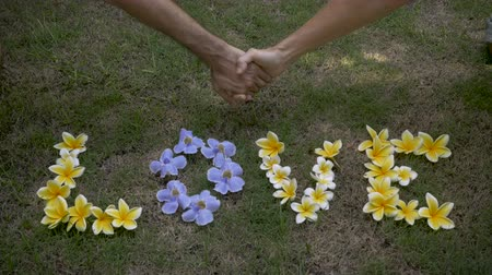çiftleşme : Two hands grab one another and hold each other above yellow and blue flowers that spell out love.