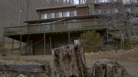 abandoned house : A log home in the woods in the winter with trees without leaves and a rotting stump in the foreground during the day - establishing dolly shot