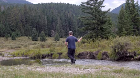 ryba : A sportsman catches a fish in a river fly fishing in the Montana wilderness.