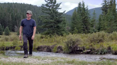 self sufficiency : A middle aged man with a fishing rod walks past the camera away from a river in the Montana wilderness without a fish. Stock Footage