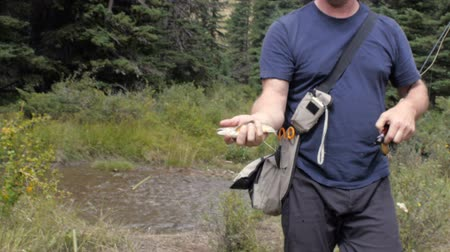 self sufficiency : A fisherman shows the camera a freshly caught trout from the mountain stream