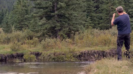 self sufficiency : A middle aged man fly fishing in a river in Montana skillfully catches a fish Stock Footage