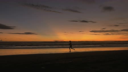shadows : The silhouette of a woman running along the beach during a dramatic sunrise or sunset in Bali, Indonesia Stock Footage
