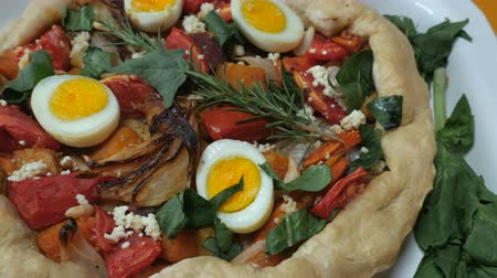 espinafre : Healthy, home made vegetarian torte with hard boiled eggs, cheese, tomatoes, onions, spinach, and rosemary dolly shot stopping on the center of the pie.