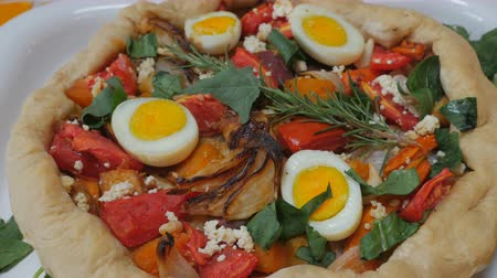 espinafre : Healthy, home cooked vegetarian pie with hard boiled eggs, cheese, tomatoes, onions, spinach, and rosemary push in dolly shot Stock Footage