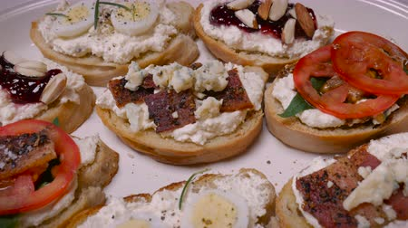 crostini : A selection of gourmet appetizers or crostinis on a plate with tomato, cheese, bacon, egg, nuts, basil, rosmary, and jam - push in