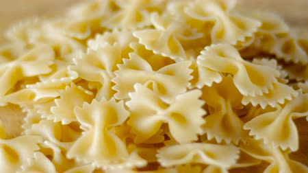 kasza manna : Bow tie pasta spinning on a wooden cutting board close up Wideo