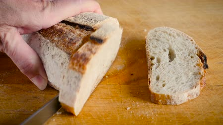 piekarz : Close up of a hand slicing a baguette with a serrated bread knife on a wooden cutting board