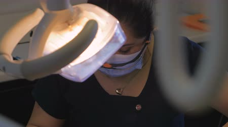 healthy office : Dolly of a hispanic dentist working in her clinic. Stock Footage