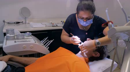 stomatologia : A Mexican woman dentist cleans a middle aged mans teeth in a modern dental office.