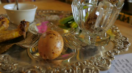 hard boiled : Fly over of a typical passover seder plate and hebrew text Haggadah including the Maror - the bitter herb, Charoset - A sweet, brown mixture representing the mortar, Karpas - A vegetable which is dipped into salt water, Zeroah - the only element of meat,