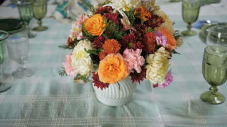 pascha : Push in of a floral center piece on a large dinning room table ready for a big celebration passover seder dinner.