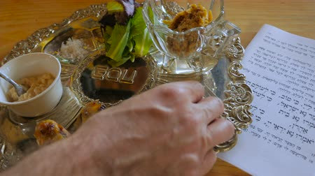 pascha : A hand puts the finishing touches on a passover seder plate next to the Haggadah and includes the Maror - the bitter herb, Charoset - A sweet, brown mixture representing the mortar, Karpas - A vegetable which is dipped into salt water, Zeroah - the only e