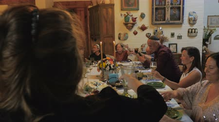 pascha : A large group of mixed generational people join in a toast as someone leads the blessing of the wine at the opening of a seder dinner. Wideo
