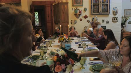 ailelerin : A large group of friends and family cheer with sparkling wine at a passover seder or jewish gathering