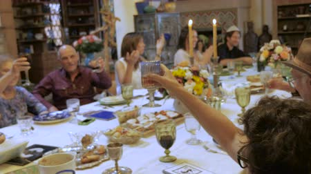 zsidó : A man wearing a yarmulke leads a toast at a large dinner table such as a passover seder or jewish cultural event - handheld