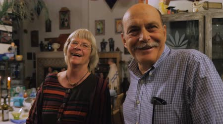 żart : A senior couple laugh and smile with each other after a dinner party