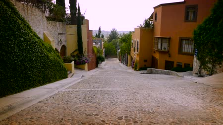 parke taşı : Slow motion steadicam of a cobble stone street with colorful houses and no cars in San Miguel de Allende