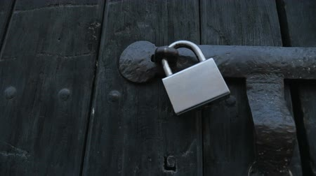 запертый : Close up of a silver lock on an old wooden door - handheld Стоковые видеозаписи