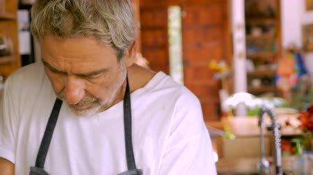 preparar : A senior man looking down while preparing food in his kitchen while wearing an apron - dolly shot Vídeos